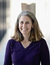 Portrait photo of smiling Dr. Jennifer Marlon against bright, blurred background.