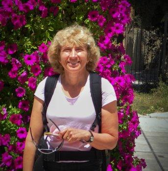 Dr. Sheila Seaman in front of purple bougnavilla bush, smiling at camera.