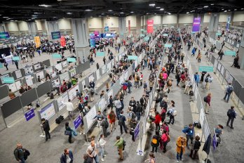Photograph looking down on the poster hall of the 2018 AGU fall meeting, with several hundred people congregated in multiple rows of poster-stands, looking at what is hung on them.