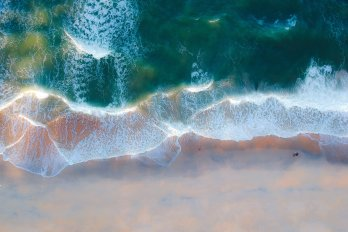 Aerial view of surf zone of beach, with green-blue water dominating top half of photograph, white foamy surf in middle, and pink-yellow beach at bottom.