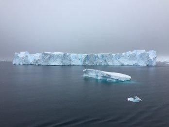 long, low iceberg floating on dark grey sea with gloomy, dark, overcast sky in background