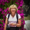 Dr. Sheila Seaman in front of purple bougnavilla bush, smiling at camera.