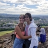 Raquel Bryant and Julie Beck facing camera in half-embrace atop rock outcrop in front of green pastoral scenery surrounding Edinburgh