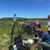 Hydrogeology students standing in a field with survey and geophysical equipment, adjacent to marshland
