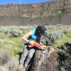 Karin Legnick in steep sided open canyon using a power tool on a boulder.